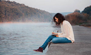 a woman writing by a lake during cocaine addiction rehab program