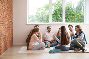 group sitting on the floor talking during the psychodynamic group therapy program in Utah