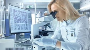 lab technician looking into microscope at sample from genetics testing program in Utah