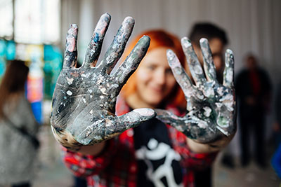 woman holding up paint covered hands during the art therapy program in Utah